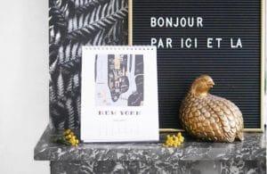 calendrier posé sur cheminée en marbre et objets déco en laiton