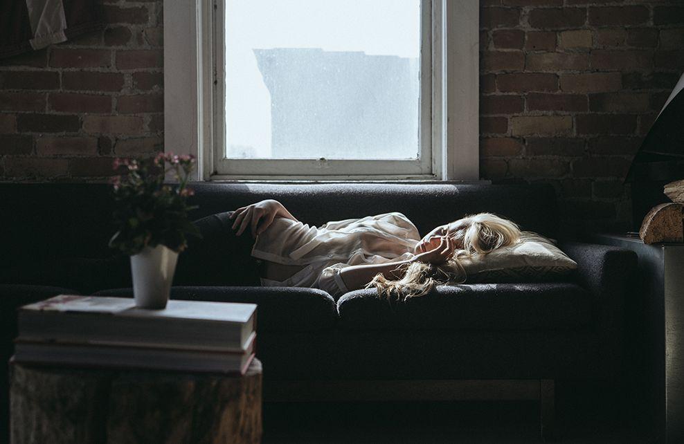 jeune fille avec mal de tete sur canapé