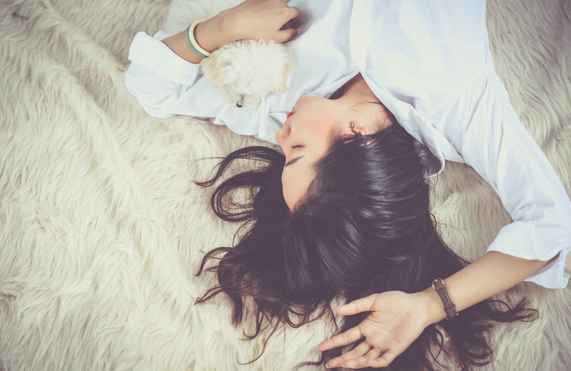 femme endormi sur un lit avec un petit chien blanc dans les bras