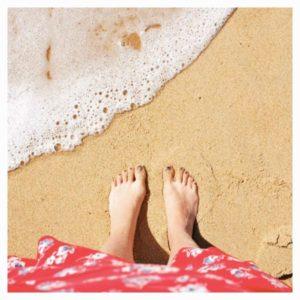 Blogueuse les pieds dans le sable à la plage
