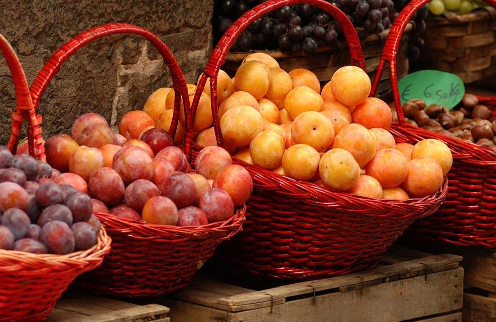 prunes présentées sur un marché dans des paniers
