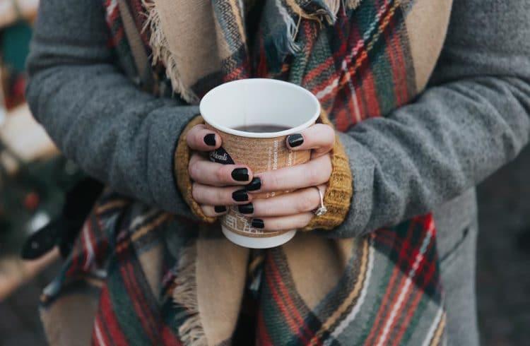 Jeune femme tenant un verre de thé dans les mains