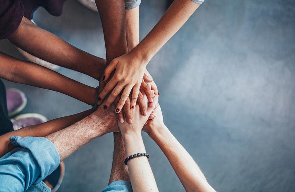 mains superposées de jeunes gens montrant l'unité
