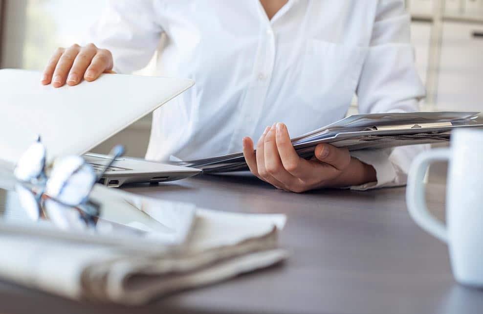 femme fermant son ordinateur portable, prête à partir du bureau