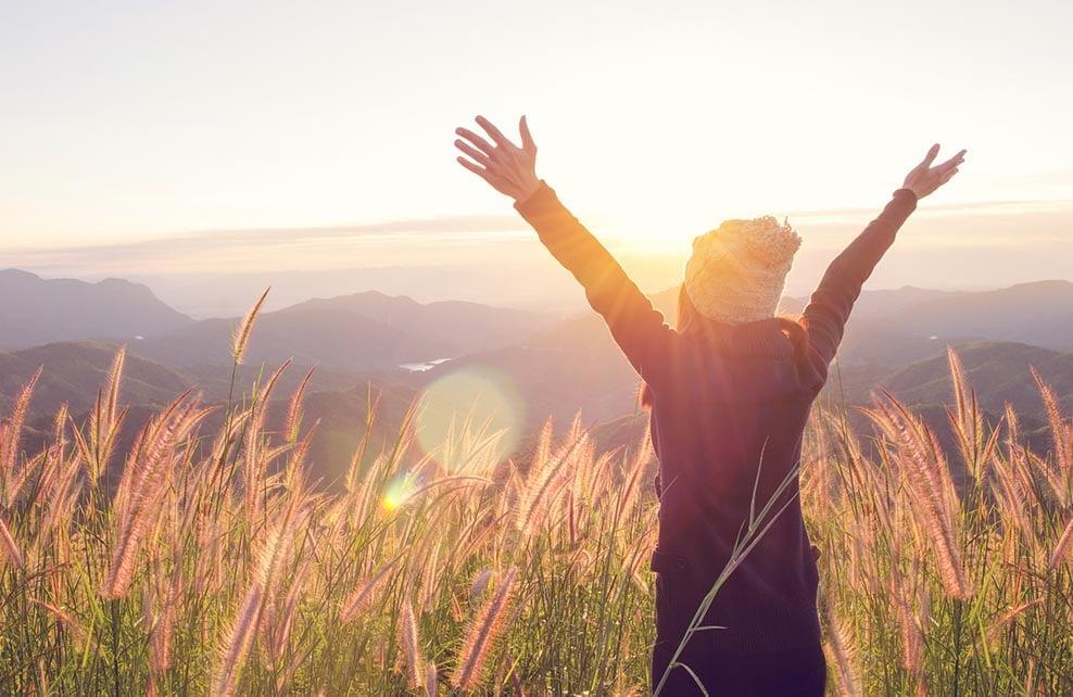 femme levant les bras au ciel sous le soleil couchant