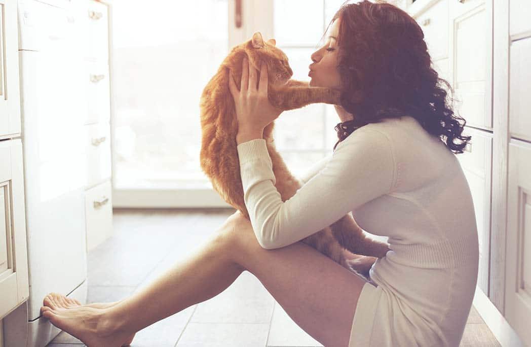 Jeune femme faisant un cain à son chat sur ses genoux