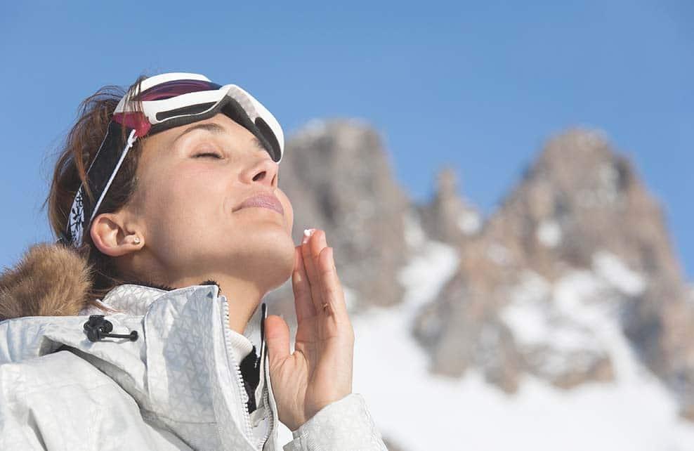 jeune femme au ski en train de s'appliquer de la crème solaire