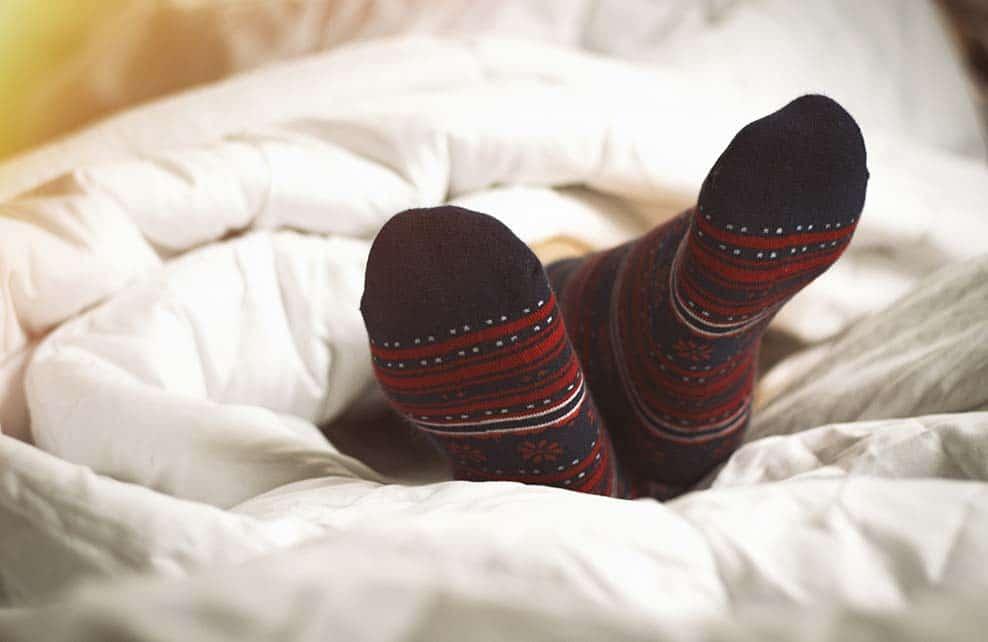 pieds d'une femme endormie dépassant de la couette