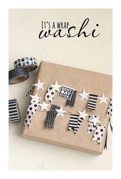 Paquet cadeau en papier craft avec guirlandes en papier noires et blanches dessus