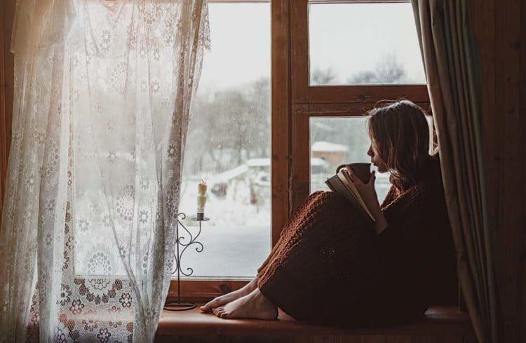 Jeune fille enveloppée dans un plaid et buvant une infusion au bord d'une fenêtre l'hiver