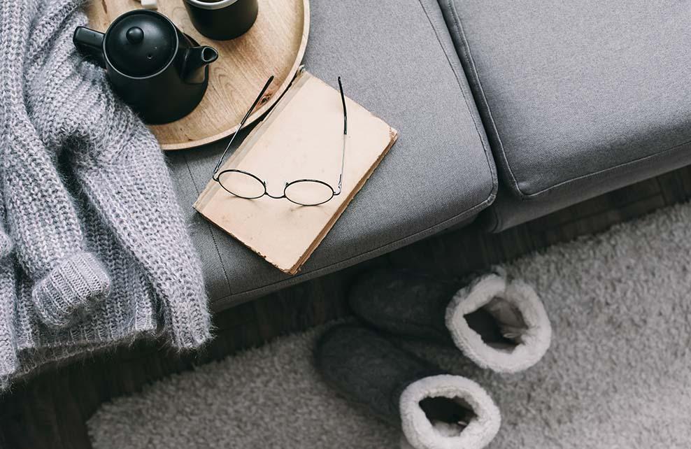 Ambiance hygge : livre, chaussons fourrés, lunettes de vue, pull en laine, theiere