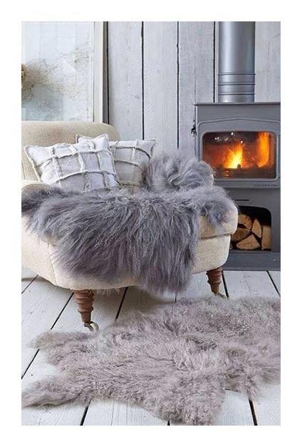 Fauteuil cosy orès d'une cheminée avec coussins et plaids