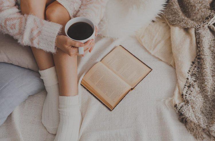 Femme sur son lit avec café et livre