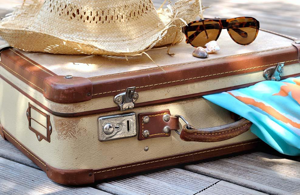 départ en vacances au soleil : valise, lunettes de soleil, chapeau de paille