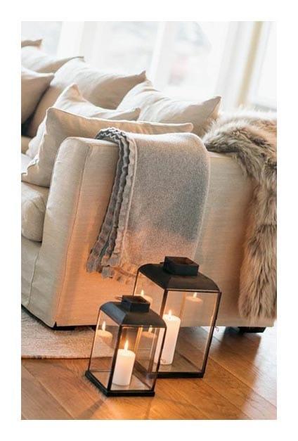 Canapé avec plaids et lanternes au sol avec bougies