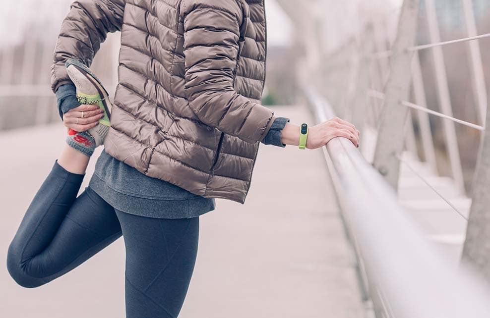 Jeune femme faisant des étirements après un footing en hiver