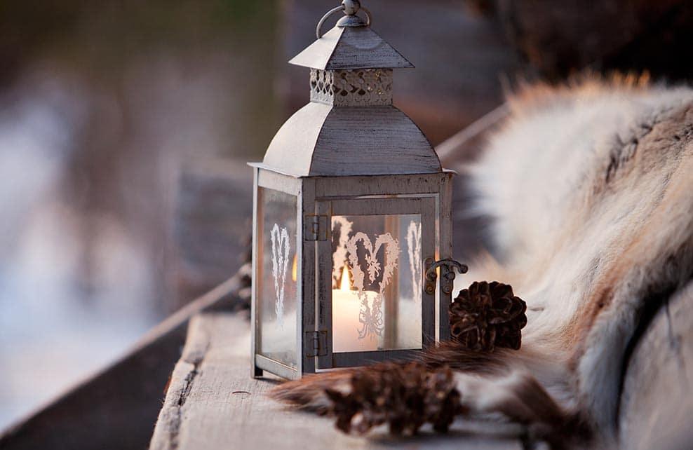 Lanterne avec plaid à l'entrée d'un porche en hiver