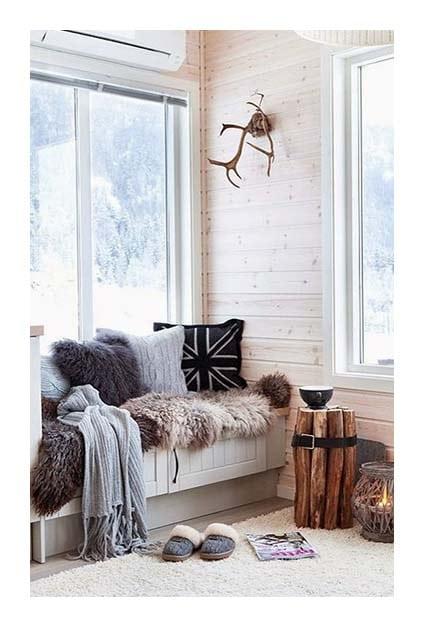 Banquette cosy avec coussins et plaids le long d'une fenêtre