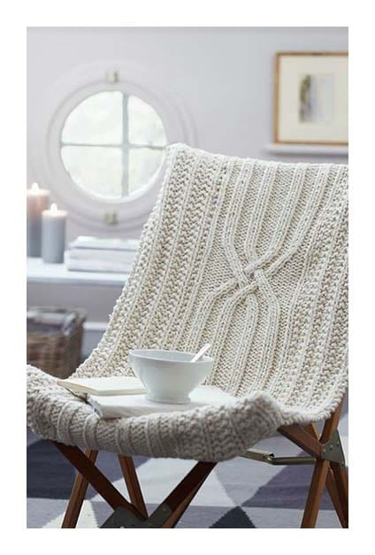 chaise cosy avec couverture laine et tasse posée dessus