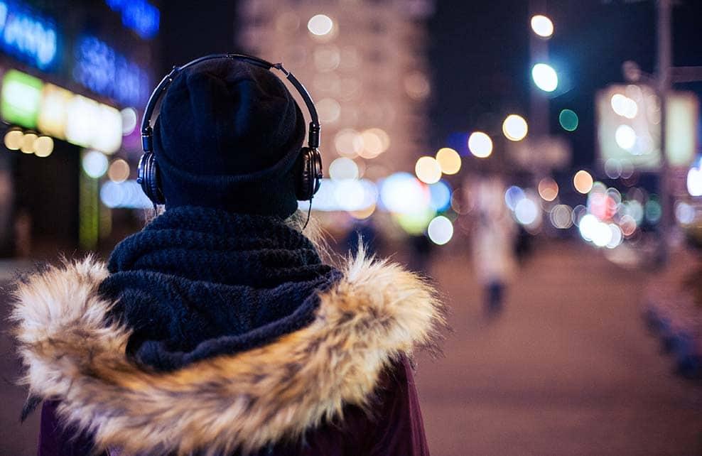 Jeune fille le soir l'hiver dans une ville illuminée avec casque audio sur les oreilles