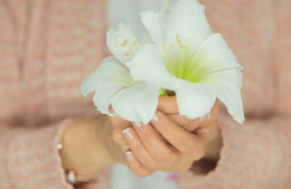 Femme tenant dans ses mains deux fleurs d'amaryllis