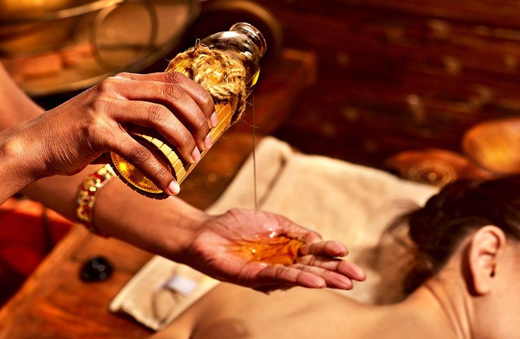 Indienne versant de l'huile dans sa main pour réaliser un massage