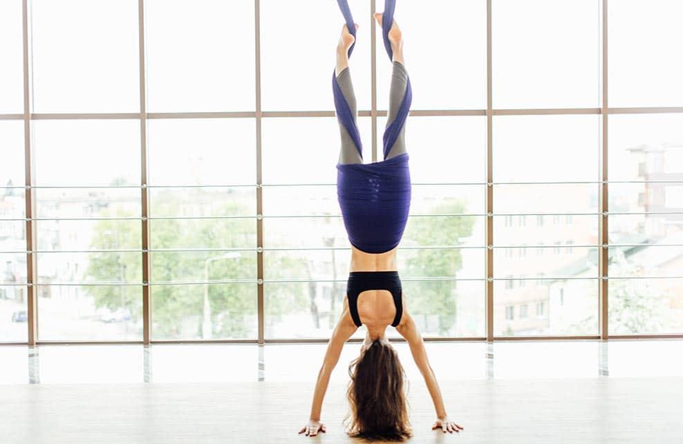 Femme pratiquant le fly yoga suspendue par les pieds