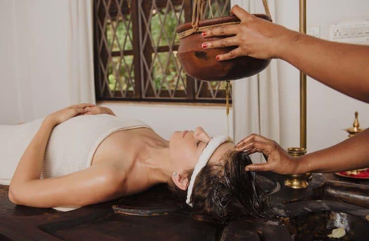 Indiennes en train de réaliser un massage ayurvédique à une jeune femme de type européen
