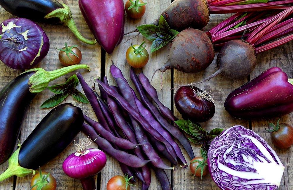 aliments violets posés sur du bois