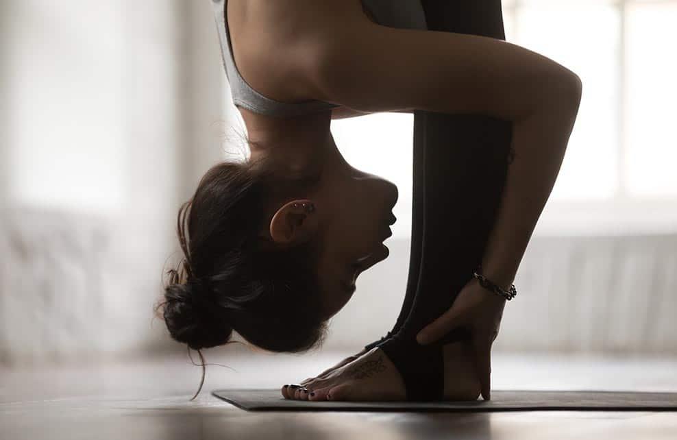 Jeune femme faisant du yoga et touchant ses mollets avec son nez