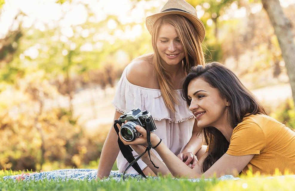 Jeunes filles assises dans l'herbe regardant des photos sur un appareil