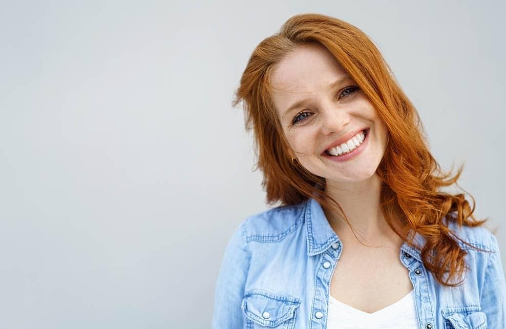 Jeune femme rousse avec une jolie peau en train de sourire