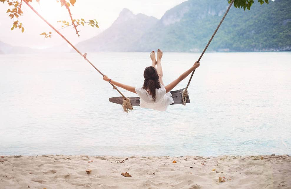 Femme sur une balancoire sur une plage paradisiaque