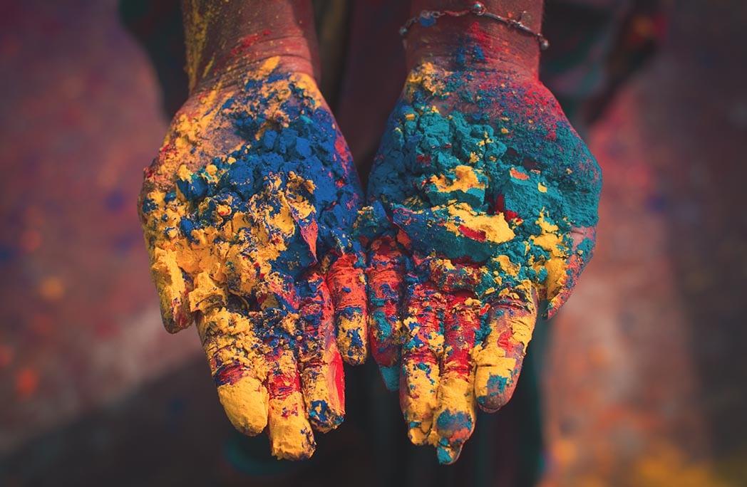 mains pleines de peinture de toutes les couleurs