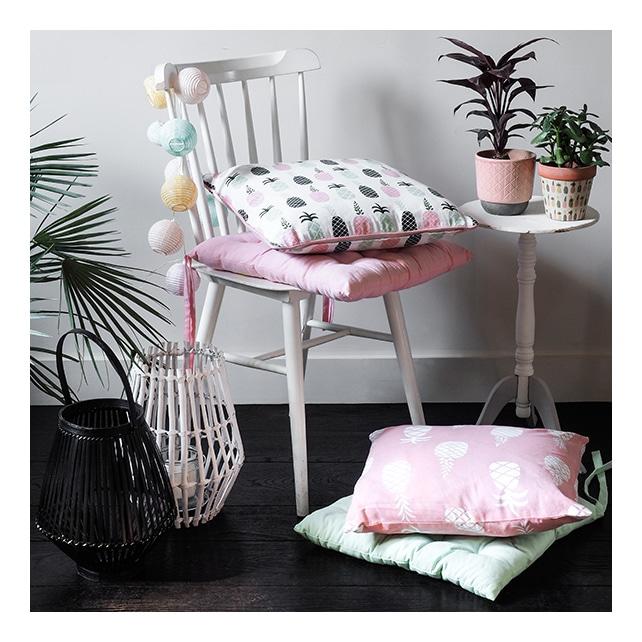 Chaise blanche, coussins à motif ananas et plantes