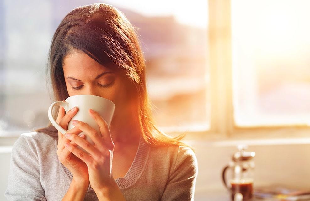 Jeune femme buvant sa tasse de café le matin