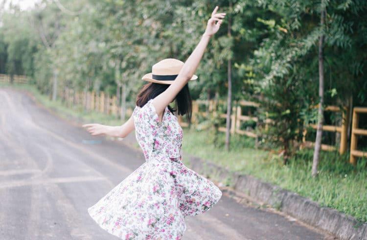 Femme avec une robe fleurie qui danse sur une route