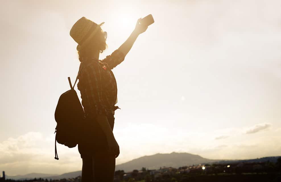 Jeune femme prenant une photo au coucher du soleil