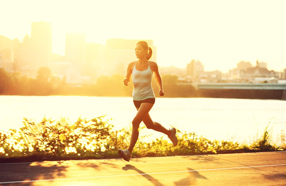 Jeune femme qui fait son jogging au coucher du soleil