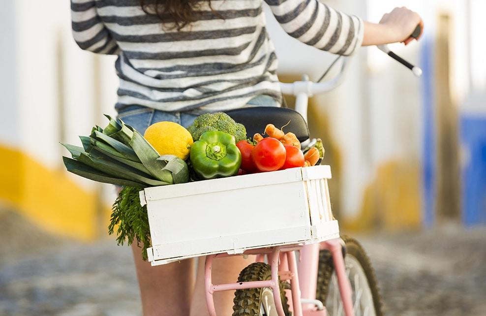 Jeune fille revenant du marché à vélo avec fruits et légumes dans un panier