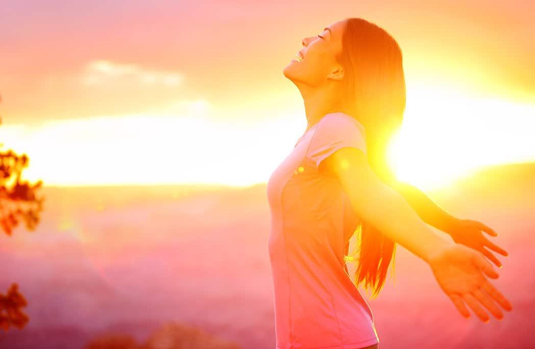 Femme étirant les bras en arrière au coucher du soleil