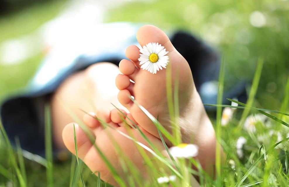 Jeune personne allongée dans l'herbe avec une pâquerette entre les doigts de pieds