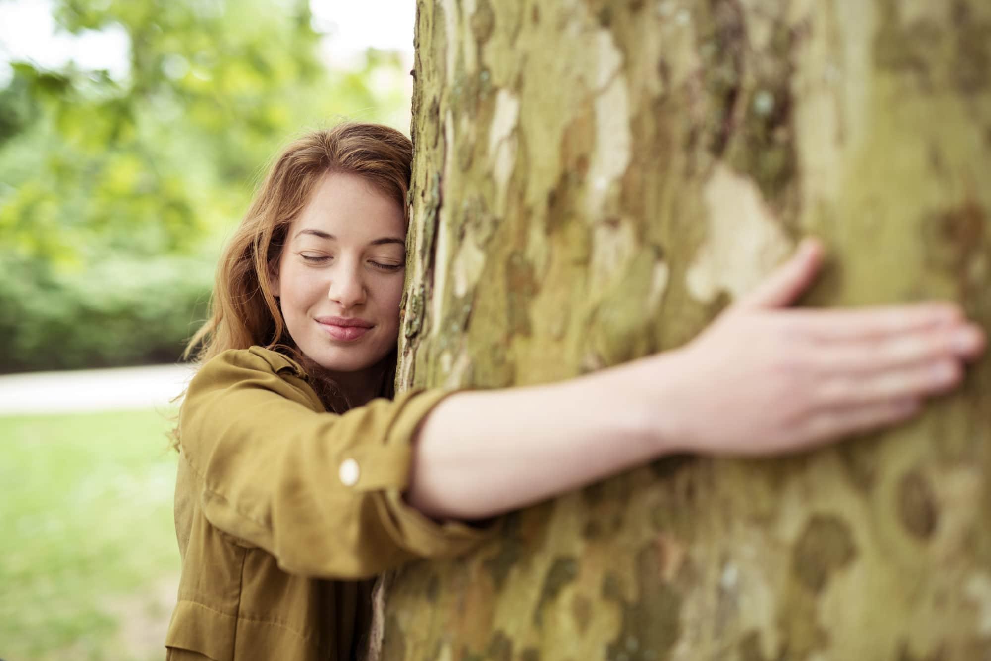 Jeune femme enlaçant un arbre, la joue contre le tronc