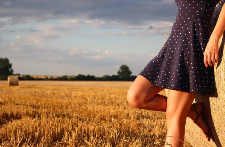 Jeune femme dans les champs adossée sur une meule de foin