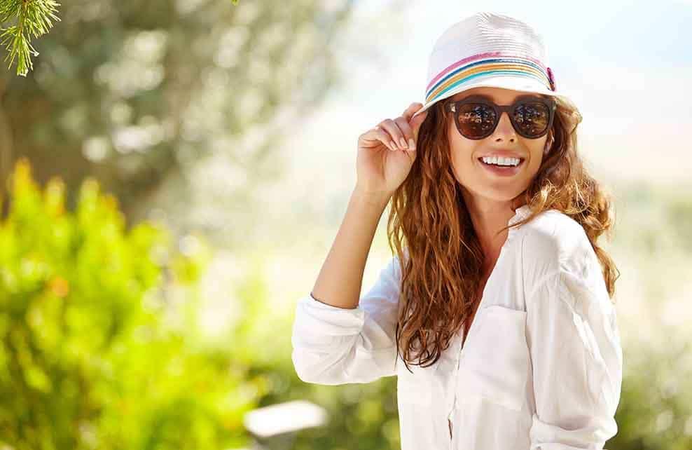 Femme souriante avec chapeau et lunettes de soleil