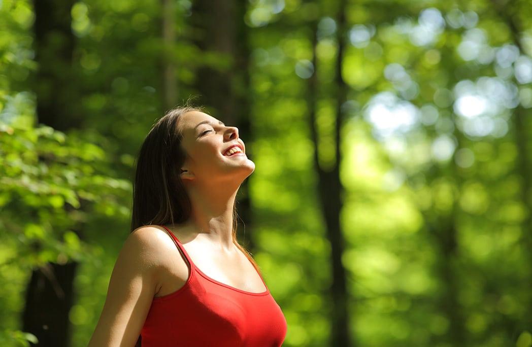 Jeune femme respirant profondément en forêt