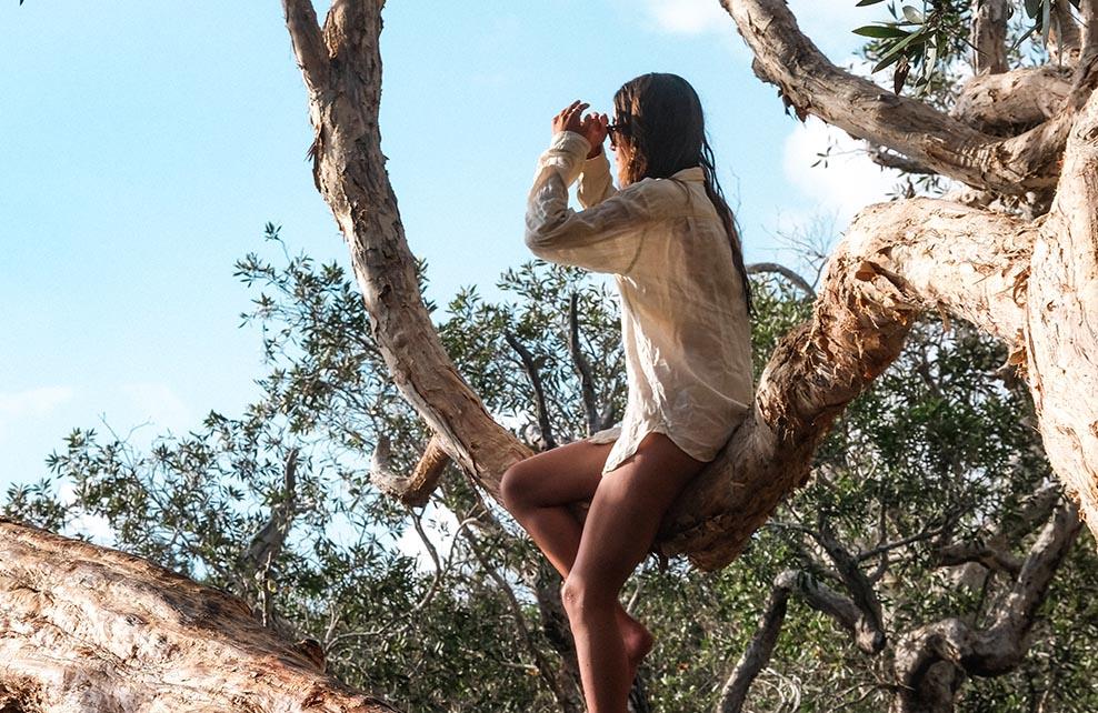 Jeune femme dans un arbre en train de regarder au loin