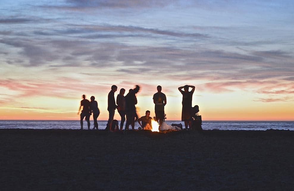 Jeunes gens autour d'un feu sur une plage au coucher du soleil