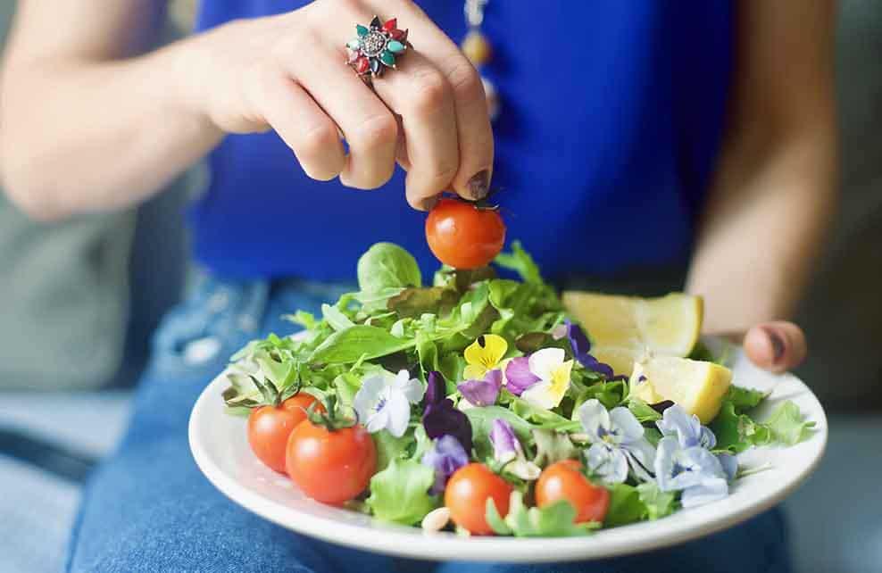Jeune femme dégustant une assiette vegan