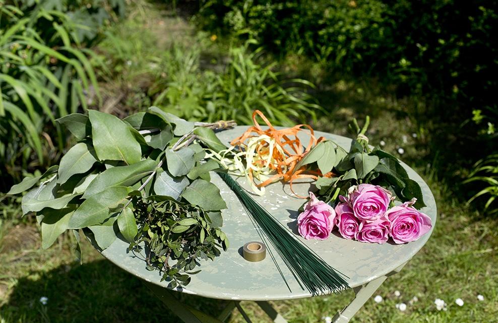 table de jardin avec fleurs, roses et outils